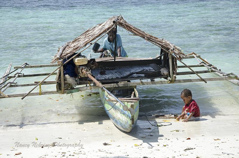 man repairing outrigger canoe