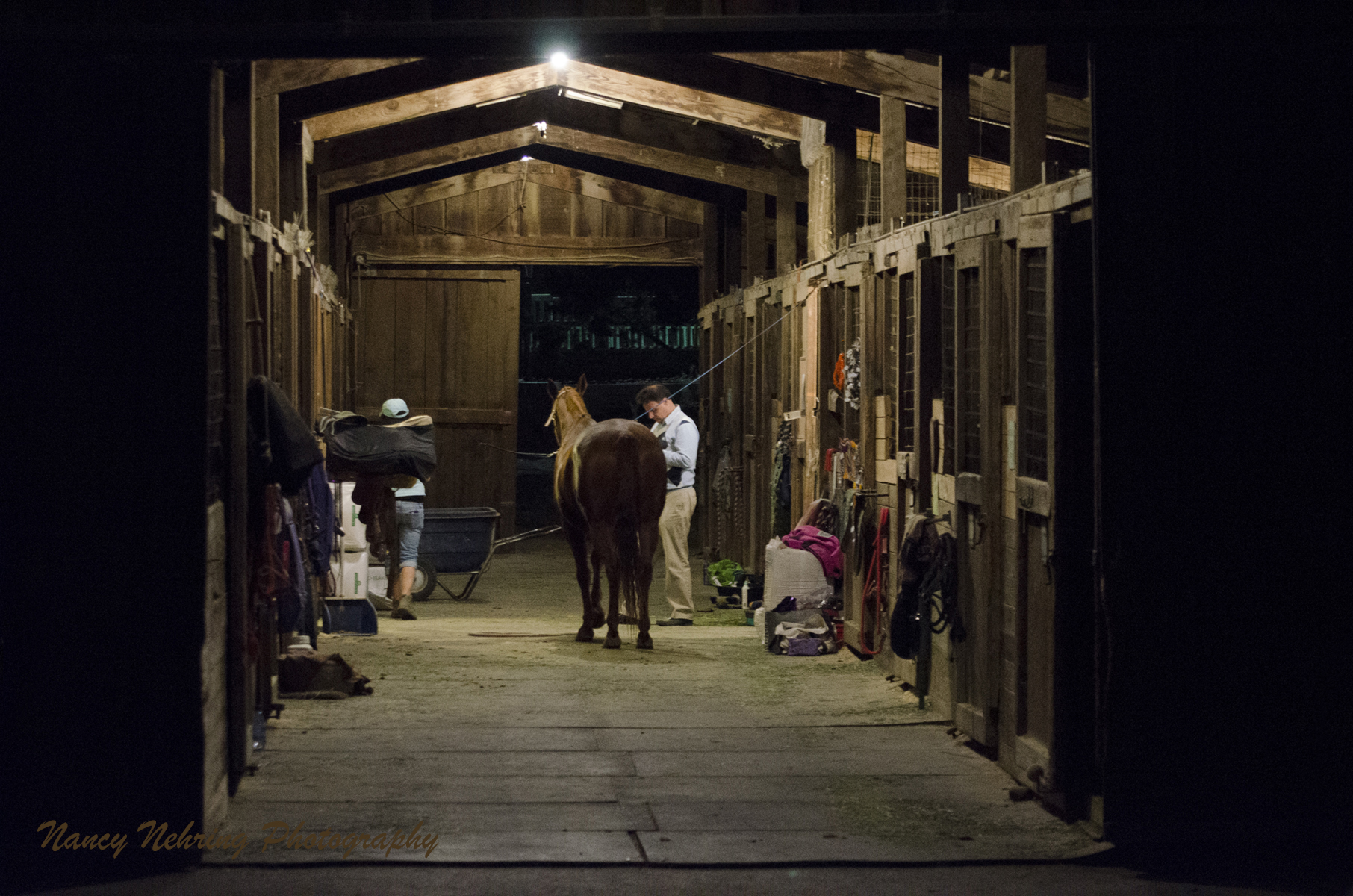 Horse stable at night with man grooming horse.