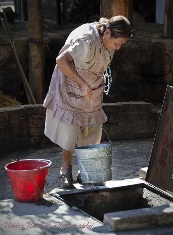 Senior Mixtec woman drawing water from an outdoor well. San Pablo Villa de Mitla, Oaxaca, Mexico.