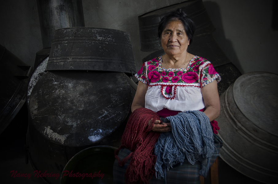 Macaria Ruiz Hernandez holding wool skeins naturally dyed with cochineal and indigo while sitting among her dye pots. Teotitlan de Valle, Oaxaca, Mexico.